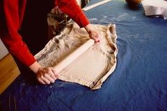 大师塑造在一块蓝色帆布的瓦器 创造性的进程 给形状您的产品 涂与滚针的黏土 免版税图库摄影