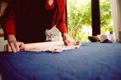 大师塑造在一块蓝色帆布的瓦器 创造性的进程 给形状您的产品 涂与滚针的黏土 免版税库存照片