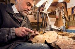 大师审查木雕刻,木匠检查完成 免版税库存图片