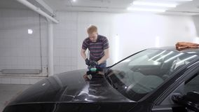 大师擦亮黑汽车表面并且申请nanoceramics防护层数在车库的 影视素材