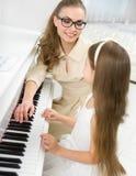 大师教小女孩弹钢琴 免版税库存照片