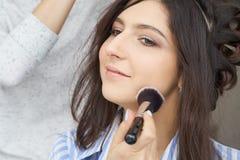 大师给予在女孩的面孔的刷子粉末,完成在美容院的天构成 免版税库存图片