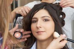 大师给予在女孩的面孔的刷子粉末,完成在美容院的天构成 库存图片