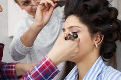 大师给予在女孩的面孔的刷子粉末,完成在美容院的天构成 库存照片