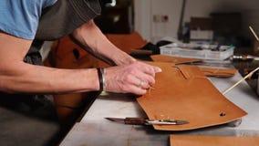 大师缝合钱包的细节用他自己的手,他在工厂 影视素材