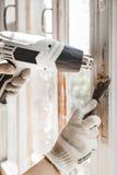 大师从窗口取消老油漆与热气枪和刮板 特写镜头 库存照片