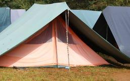 大帐篷在阵营的绿色和橙色小屋里 图库摄影