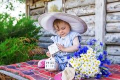 大帽子的女婴坐一个木大厦的背景 有camomiles和矢车菊的小女孩 库存图片