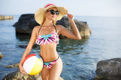 大帽子的美丽的亭亭玉立的妇女在海滩 库存图片