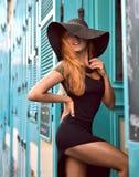 大帽子的获得年轻愉快的俏丽的妇女笑和在t的乐趣 免版税库存图片