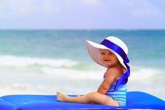 大帽子的逗人喜爱的小女孩在夏天海滩 免版税库存图片