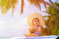 大帽子的逗人喜爱的小女孩在夏天海滩 图库摄影