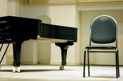 大平台钢琴和椅子 库存图片