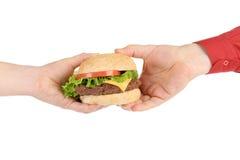 大开胃汉堡包在手中。 免版税库存图片