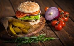 大开胃汉堡用牛肉、土豆和乳酪木表面上 免版税图库摄影