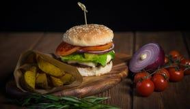 大开胃汉堡用牛肉、土豆和乳酪木表面上 图库摄影