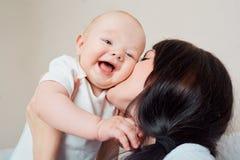 大微笑小孩 拥抱妈妈的婴孩 笑在胳膊的孩子  图库摄影