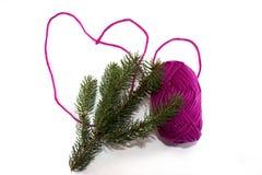 大心脏由螺纹制成紫色丝球与杉木分支的 免版税库存照片
