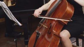 大提琴球员 弹有弓的大提琴手手大提琴 乐谱架 并且钢琴演奏家 股票录像