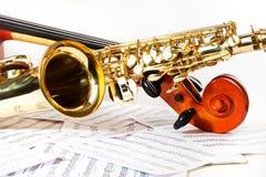 大提琴调整的钉和发光的金黄女低音萨克斯管 图库摄影