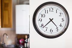 大时钟在白色墙壁登上了有厨房背景 免版税库存照片