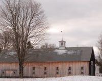 大有白色圆屋顶的新英格兰褐色木谷仓在一冷的黑暗的1月下旬天 免版税库存图片