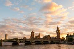 大本钟和议会与威斯敏斯特桥梁在伦敦日落的 免版税库存图片
