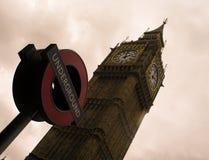 大本钟塔和伦敦地铁的标志反对多云天空的 库存照片