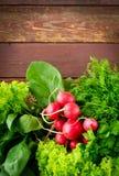 大束新有机菜、萝卜、菠菜、沙拉和绿色在老木桌,特写镜头上 库存照片