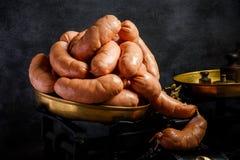 大束未加工的短的浓熏肉香肠在螺旋滚动了在等级 免版税库存图片
