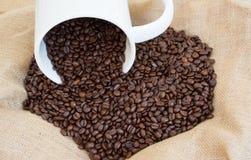 从大杯子的溢出的咖啡豆 免版税库存照片
