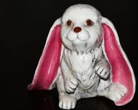 大桃红色懒散的有耳的陶瓷兔宝宝为假日 图库摄影