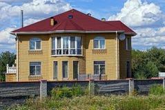 大棕色房子在篱芭后的红色铺磁砖的屋顶下在草 图库摄影