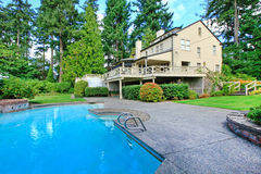 大棕色房子外部与夏天庭院和游泳池 免版税库存照片