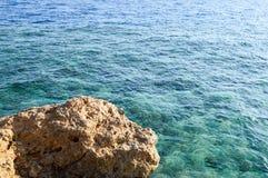 大棕色美丽的石头,一个岩石在反对大海和拷贝空间背景的海  抽象背景异教徒青绿 库存照片