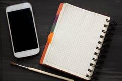 大模型和智能手机在背景老黑桌上 免版税库存图片
