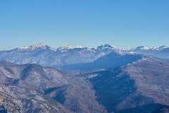 大横向山山 在前面和中立立场有一个森林,在山的积雪的峰顶后 美好的bl 图库摄影