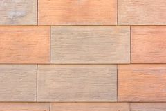 大橙色和米黄平板墙壁  大砖,自然石头的模仿 免版税库存照片
