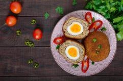 大水多的炸肉排充塞用在黑暗的木背景的煮沸的鸡蛋 免版税库存图片
