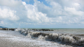 大波浪在多岩石的海滩滚动 库存照片