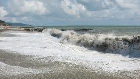 大波浪在多岩石的海滩滚动 免版税库存图片