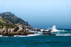 大波浪打破反对点罗伯斯岩石和峭壁在有雾和有薄雾的天空下 库存照片