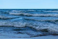 大海海边在日落光以后的晚上挥动 免版税库存图片