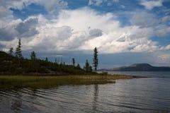 大湖,落叶松属和白色云彩岸的  库存图片