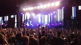 大激动的愉快的愤怒的人民拥挤跳高在明亮的轻的露天阶段音乐会摇滚小组违规记录的慢动作 股票录像