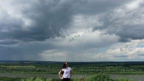 大灰色云彩和自然的背景的小妇女 股票录像