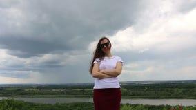 大灰色云彩和自然的背景的小妇女 股票视频