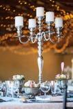 大烛台&花在桌上在结婚宴会 免版税图库摄影