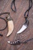 大熊牙和骨头垂饰从在棕色bac的鹿雕刻了 库存照片