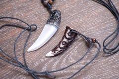 大熊牙和骨头垂饰从在棕色bac的鹿雕刻了 免版税库存照片